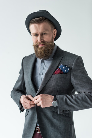 Man with vintage mustache and beard buttoning his jacket isolated on light background Stock Photo
