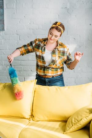 beautiful woman dusting yellow sofa at home Stock Photo