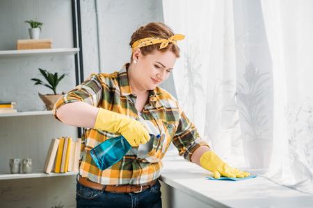 beautiful woman dusting windowsill at home
