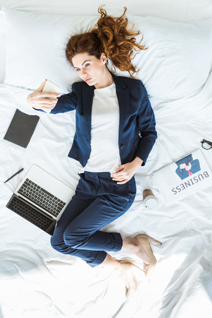 Top view of businesswoman in suit taking selfie in bed among folders and documents
