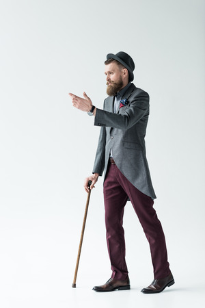 Handsome man in vintage style clothes holding cane on light background Stockfoto