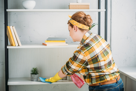 side view of beautiful woman dusting shelves at home
