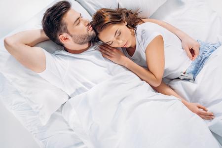 Draufsicht des jungen Paares, das zusammen im Bett schläft