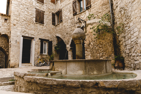 atrium of ancient buildings at old town with beautiful fountain, Peille, France 版權商用圖片