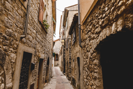 narrow street with ancient stone buildings at old european town, Peille, France