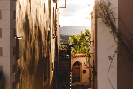 narrow street with ancient buildings at old town with sunset sky on background, Cannes, France 版權商用圖片