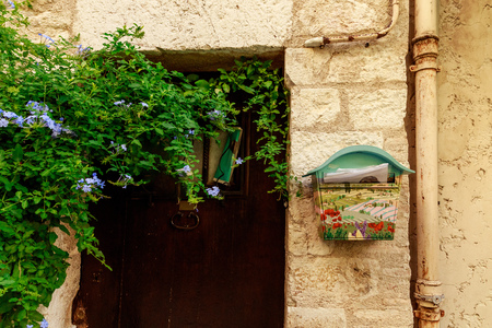 ANTIBES, FRANCE - 17 SEPTEMBER 2017: close-up shot of door of ancient european building with wall covered with vine and decorated mailbox, Antibes, France Editöryel