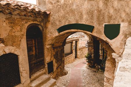 arch and ancient grungy buildings at old town, Eze, France