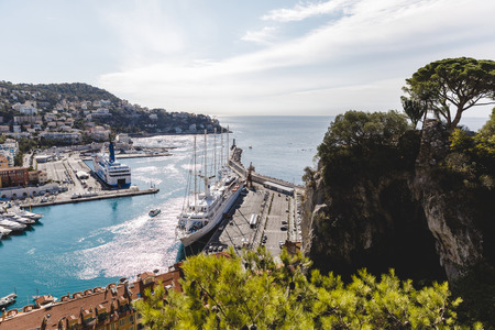 NICE, FRANCE - 17 SEPTEMBER 2017: old european city located on seashore with lot of ships in harbour 報道画像