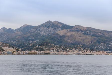 coastal city under rocky mountain on cloudy day, Nice, France
