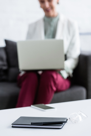 selective focus of businesswoman using laptop, smartphone, diary, pen and glasses lying on table on foreground