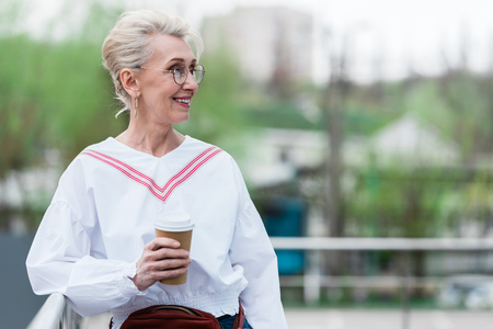 beautiful senior woman in trendy outfit holding disposable cup of coffee in park