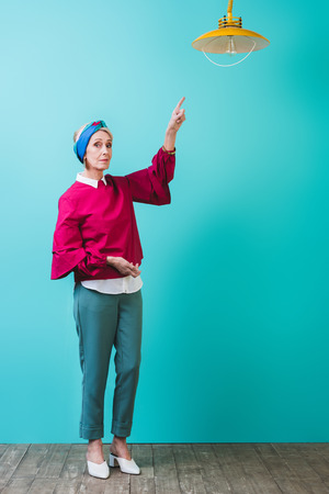 fashionable senior woman pointing at lamp in room with turquoise wall Stock Photo