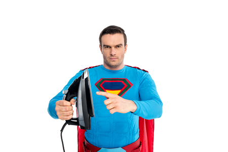 handsome male superhero pointing with finger at iron and looking at camera isolated on white Imagens