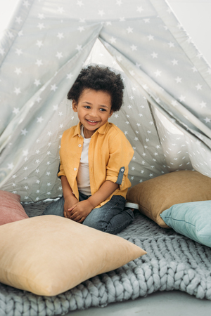 little smiling african american boy sitting in teepee at home