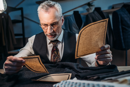 handsome mature tailor working with cut patterns at sewing workshop in late evening Stock Photo