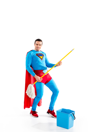 handsome superhero having fun with mop and smiling at camera on white