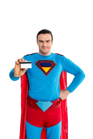 handsome man in superhero costume holding credit card and smiling at camera isolated on white Imagens