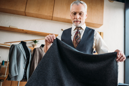 handsome mature tailor with grey cloth at sewing workshop