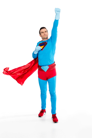full length view of male superhero in rubber gloves raising hand and looking up isolated on white Imagens