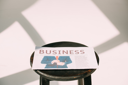 close-up view of business newspaper on wooden stool on white Standard-Bild - 106802778
