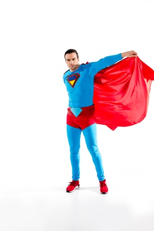 handsome man in superhero costume and cloak looking at camera isolated on white
