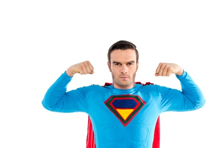 handsome superhero showing muscles and looking at camera isolated on white