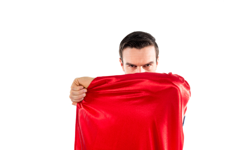 handsome male superhero hiding behind cloak and looking at camera isolated on white