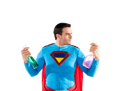 handsome superhero holding plastic spray bottles with cleaning liquid isolated on white Imagens - 106807239