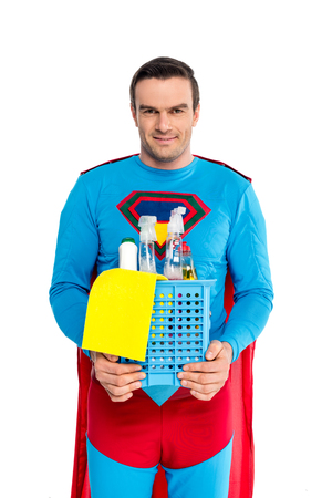 handsome man in superhero costume holding cleaning supplies and smiling at camera isolated on white Imagens