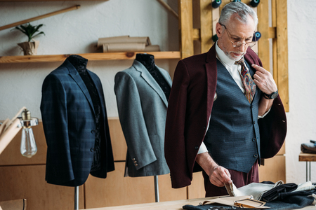 handsome mature tailor in stylish clothing working at sewing workshop
