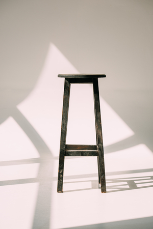 single empty tall wooden stool on white Standard-Bild - 106808429