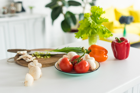 close up view of arranged fresh vegetables and mushrooms on tabletop in kitchen