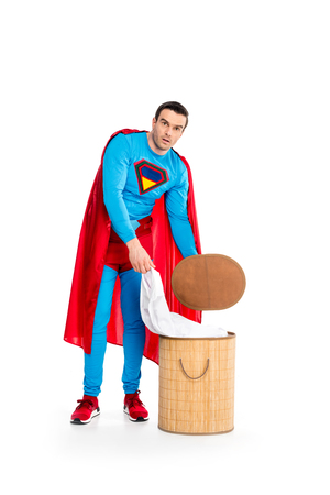 handsome male superhero putting clothes in laundry basket and looking at camera isolated on white