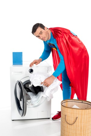 washing clothes in washing machine and looking at camera on white Standard-Bild - 106810283