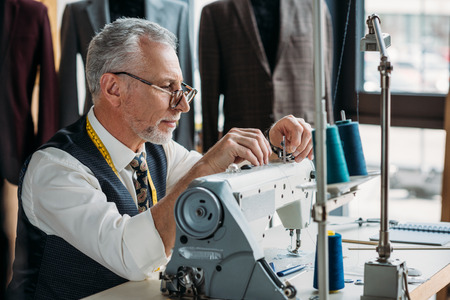 confident mature tailor working with modern sewing machine at workshop Stockfoto