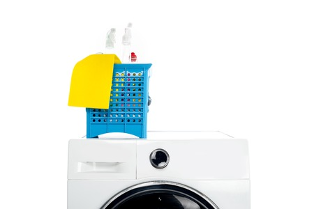 plastic basket with cleaning supplies on washing machine isolated on white