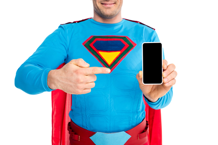 cropped shot of man in superhero costume pointing with finger at smartphone with blank screen isolated on white Imagens
