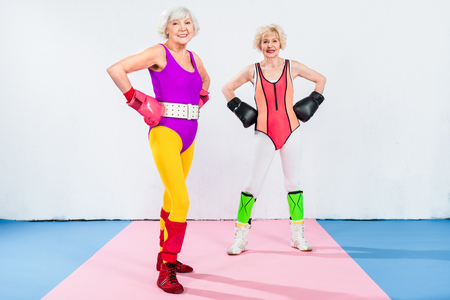 full length view of sportive senior ladies in boxing gloves standing with hands on waist and smiling at camera