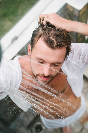 overhead view of sexy handsome man taking shower outdoors in Bali, Indonesia Stock Photo
