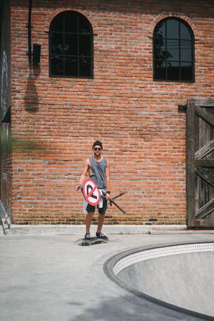 handsome skater holding road sign near skatepark Reklamní fotografie