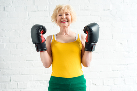 happy sporty senior woman in boxing gloves smiling at camera Stock Photo
