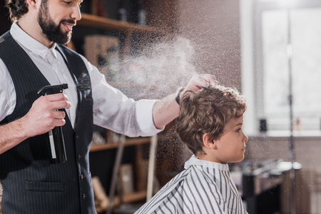 smiling bearded barber combing and spraying hair of little kid Stock fotó