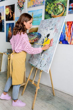 side view of beautiful female artist painting in workshop