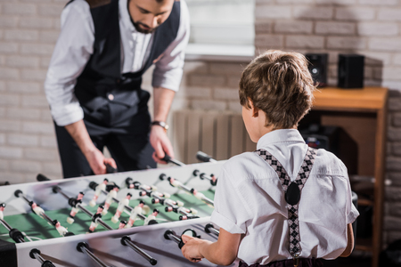 father and son in vintage clothing playing table football