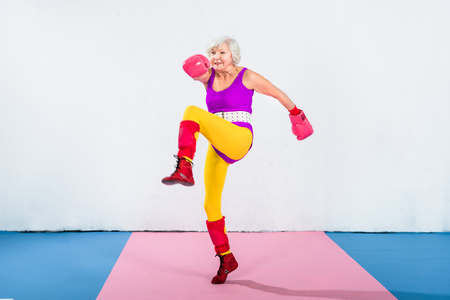 full length view of senior female boxer training and looking away