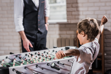 stylish little kid playing table football with father