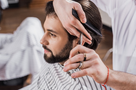 cropped shot of barber cutting hair of customer with scissors Фото со стока