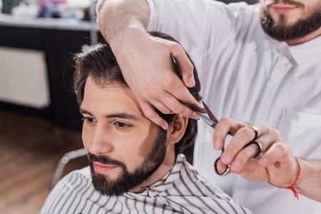 smiling bearded man getting haircut in barbershop Фото со стока