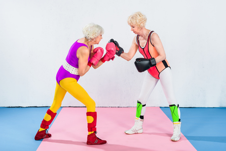 side view of senior sportswomen in boxing gloves fighting and looking at each other